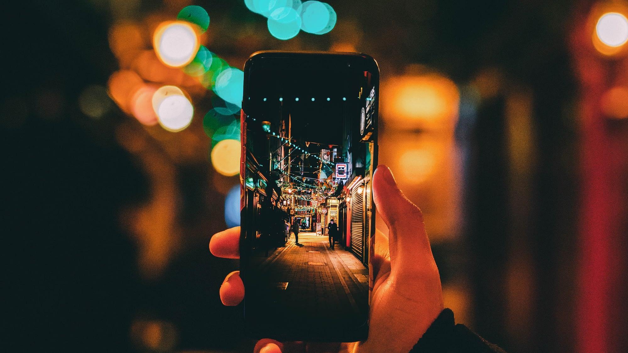 Une personne prend une photographie d'une rue avec son smartphone